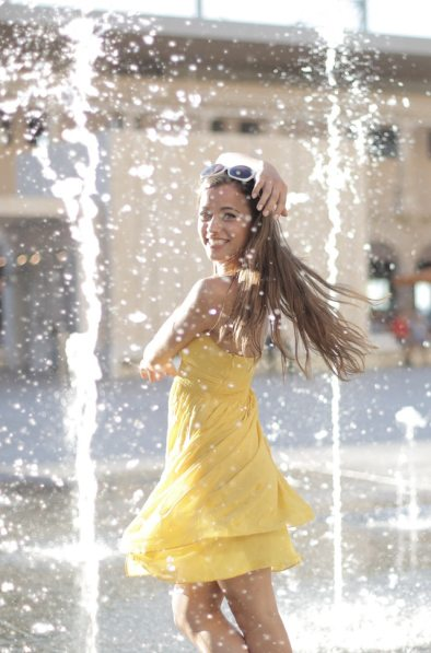 woman-in-yellow-dress-standing-near-water-fountain-while-3811461